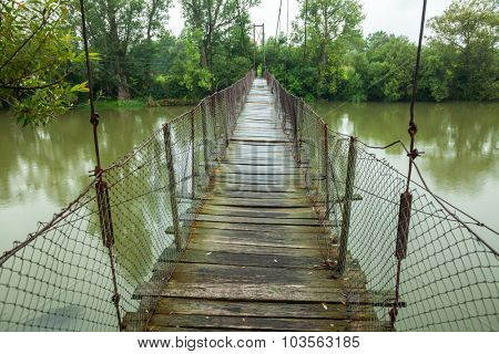 Rickety foot bridge over muddy water