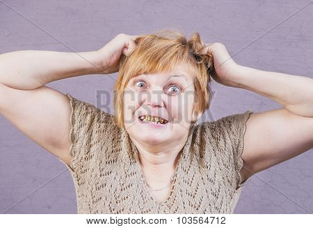 Very emotional angry woman with gold teeth on a gray background.