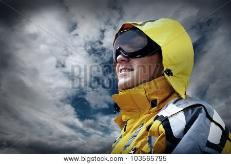 Portrait of man wearing a helmet and glasses on the background of sky with clouds