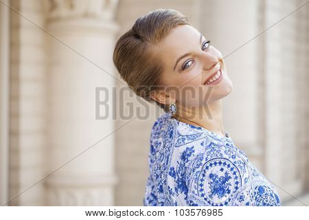 Close up portrait of a beautiful young blonde woman in blue dress, outdoors