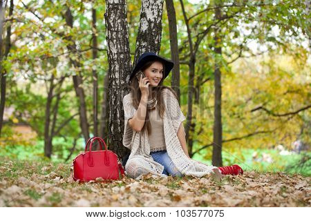 Young happy beautiful woman calling by phone in the autumn park