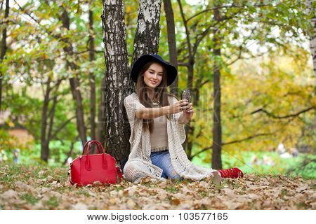 Young beautiful woman in a hat photographing themselves on a cell phone while sitting in the autumn forest