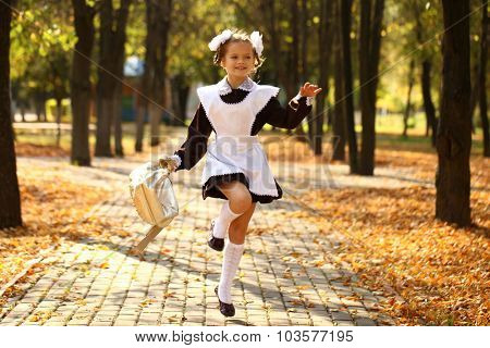 Happy little schoolgirl run home from school, outdoor autumn park