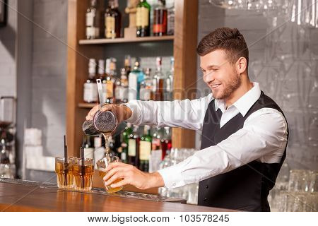 Attractive male barman is making cocktail in bar
