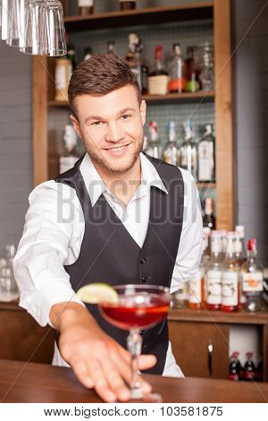 Handsome male bartender is giving drink to customer