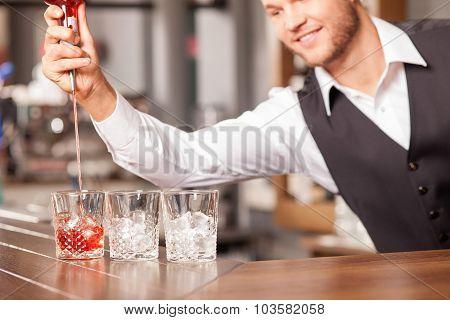 Cheerful male bartender is preparing beverage in bar