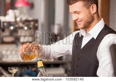 Cheerful young bartender is working in pub