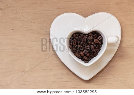 Heart Shaped Cup With Coffee Beans On Wooden Table