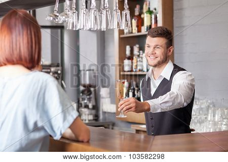 Handsome young barman is receiving order from customer