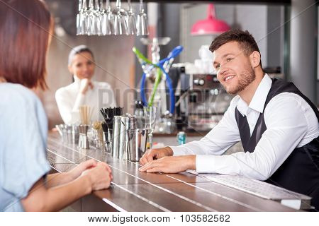 Attractive young barman is flirting with female customers