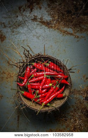 Red Hot Chili Peppers In Coconut Shell On Rusty Steel  Background