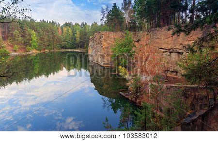 Morning scene with rocky lake shore in pine forest