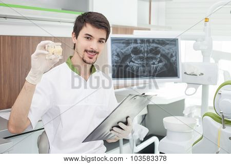 Handsome young dentist is working in laboratory