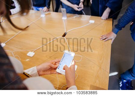 PARIS FRANCE - OCT 3 2015: Customer checks the new iPhone 6s displayed at the Apple Store Opera with the App Store Top Apps