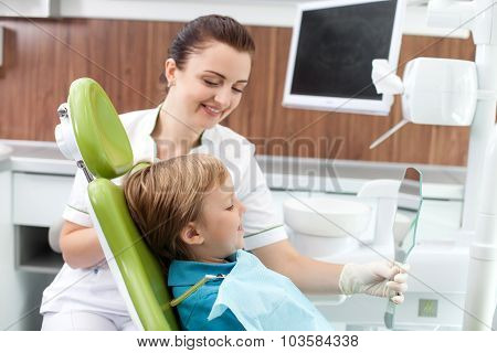 Cute male child is satisfied with work of dental doctor
