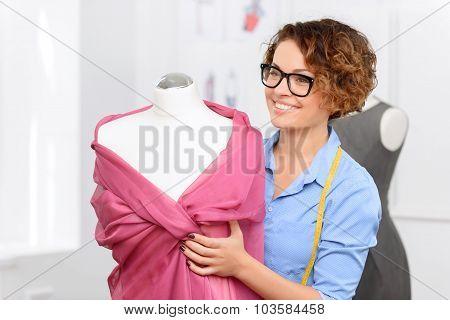 Pleasant designer standing near model