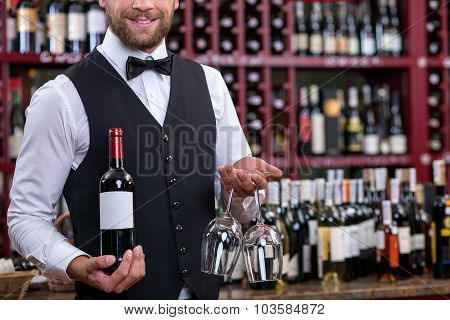 Cheerful young waiter is carrying alcohol drink in cellar