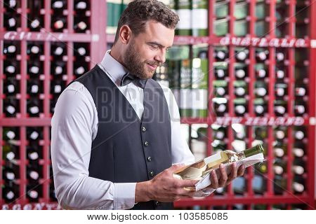 Attractive young male sommelier is working in cellar
