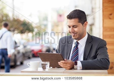 Handsome young businessman is using tablet in cafeteria