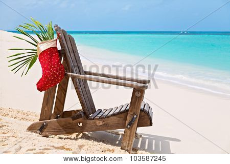 Sun Lounger With Santa Sock At Beautiful Tropical Beach With White Sand And Turquoise Water, Christm