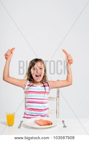 Happy cheerful girl playing with her food, a healthy attitude towards vegetables and fresh produce