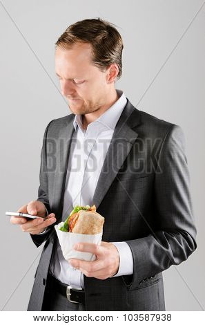 Annoyed businessman with take away lunch sandwich working on his phone texting a message