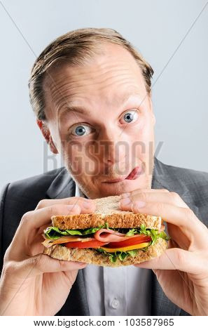 Funny humourous man eating a sandwich with exagerrated wide eye comical expression and sticking his tongue out