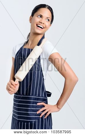 Passionate baker chef in apron holding a rolling pin