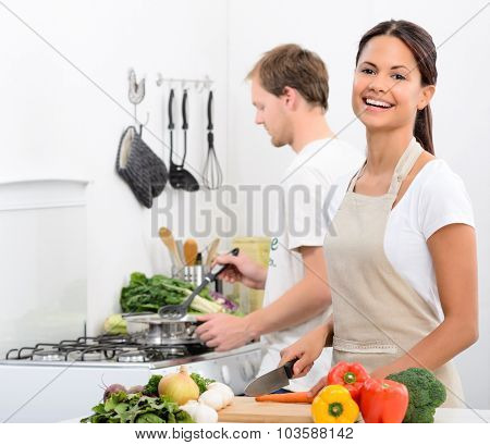 Happy smiling woman in kitchen with fresh produce vegetables preparing for a healthy meal, with partner husband cooking in background