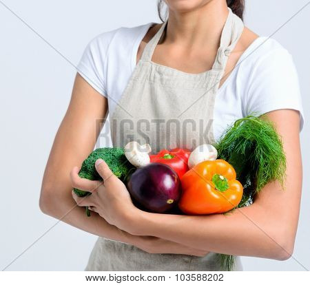 Portrait of young beautiful woman holding raw vegetables in her arm, peppers, broccoli, dill, mushrooms, aubergine