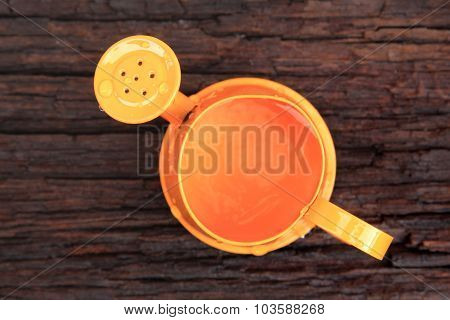 Orange Watering Can On Old Wood Background