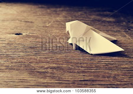 an origami bird on a rustic wooden surface, with a retro effect