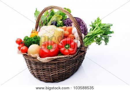 Basket full of fresh summer organicc produce vegetables from the farmers market, tomatoes, peppers, capsicums, celery, cabbage, cauliflower, mushroom, leafy greens