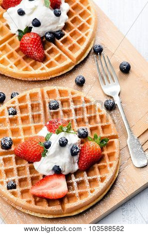 Belgian waffles with fresh fruit and sprinkled with icing sugar