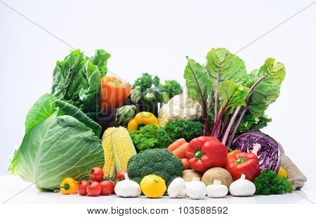 Fresh raw organic vegetable produce, assortment of corn, peppers, broccoli, mushrooms, beets, cabbage, parsley, tomatoes, isolated on light background