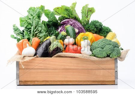 Crate of raw fresh vegetables from the farmers market, assortment of corn, peppers, broccoli, mushrooms, beets, cabbage, parsley, tomatoes, isolated on light background