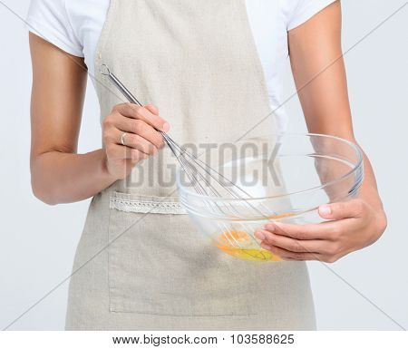Pair of hands beating and holding a glass bowl with eggs