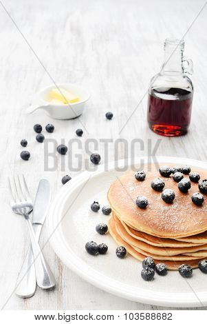 Blueberry pancake stacks with icing sugar, butter and maple syrup