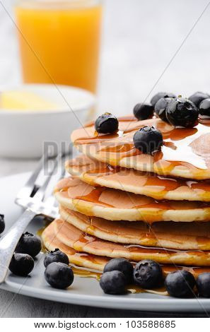 Delicious breakfast of pancakes with blueberries and orange juice