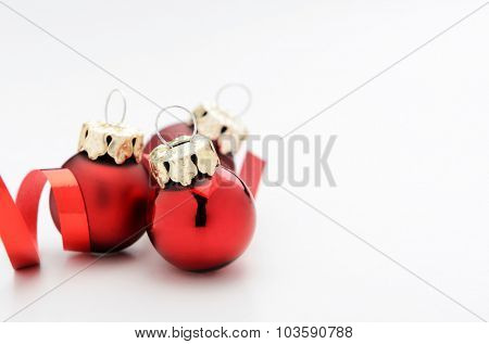 Red christmas baubles decoration with ribbon isolated on white