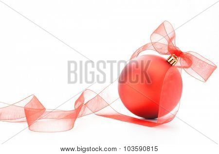Red christmas bauble decoration with organza translucent ribbon isolated on white