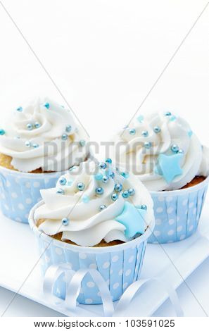 Blue theme cupcakes with white butter cream frosting and baby blue decorations