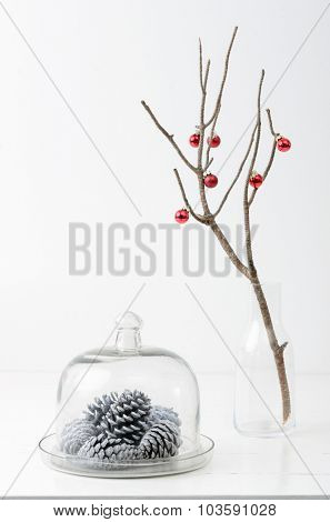 Christmas decoration ornaments, silver white pine cones in glass dome, bare branch in vase with red xmas baubles, plenty of copy space