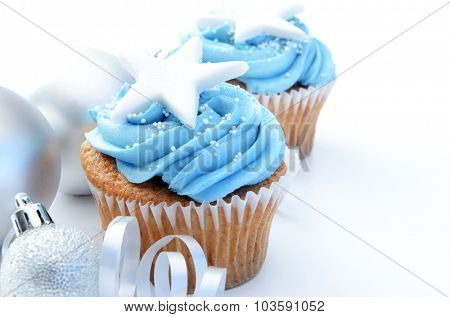 Christmas party cupcakes in blue icing, silver ornaments and ribbons