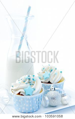 White christmas cupcakes with silver baubles and a bottle of milk