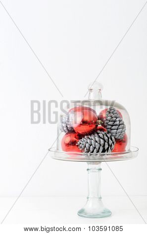 Christmas interior table decoration in simple, minimalist, elegant style with red baubles and pine cones in glass dome, plenty of copy space