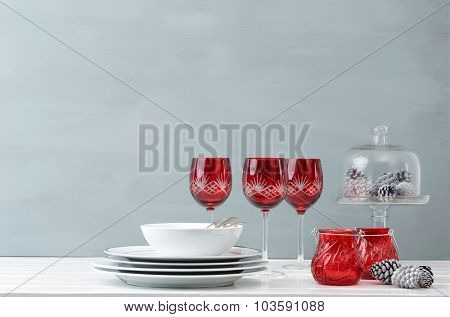 Modern christmas decoration table display with crockery and festive holiday red wine glasses