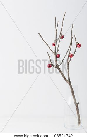 Bare branch with red christmas bauble minimalist, elegant style, plenty of copy space