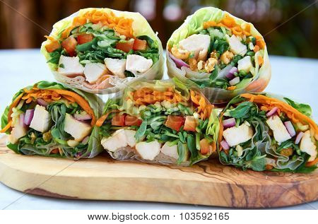 Cross section of healthy vegetable wraps with carrots, greens and chicken