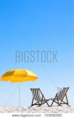 Rear view of two deck chairs and a beach umbrella with clear blue skies